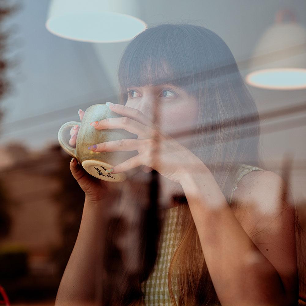Naine mõtiskleb kohvikus