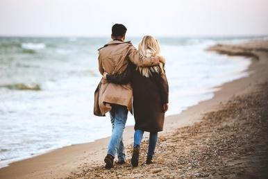 Suhtes paar jalutab rannal