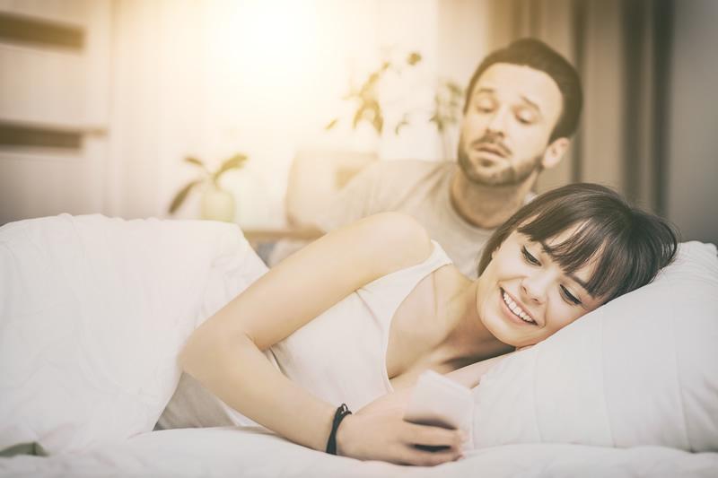 Kaaslasega voodis, naine telefonis
