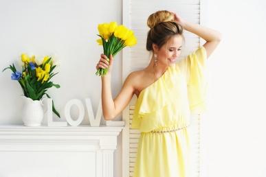 Ilus naine tulpidega kollases