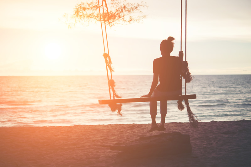Naine üksi kiigub mere ääres