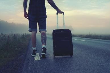Mees läheb kohvriga teel