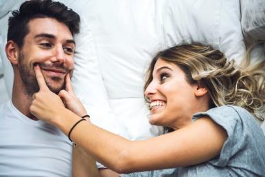 Õnnelik paar kodus voodis mehel suu kõrvuni