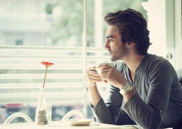 Mees istub akna all üksinda ja joob kohvi