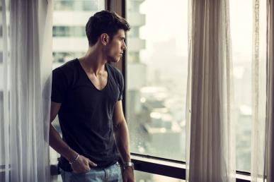 Mees vaatab üksinda kodus aknas välja