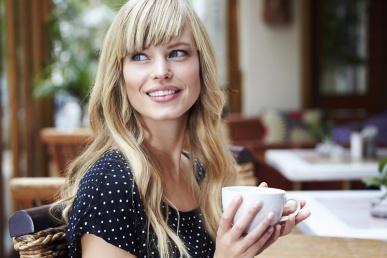 Õnnelik vallaline naine kohvikus naeratab