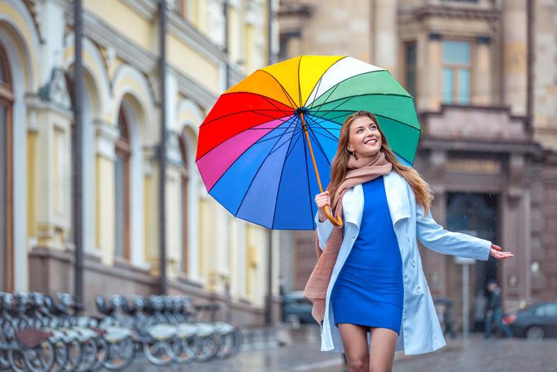 Rõõmus naine vihmavarjuga on valmis uut armastust leidma