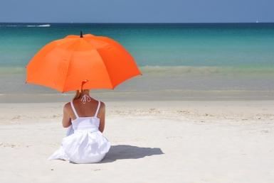 Vallaline naine istub rannal uhke varjuga