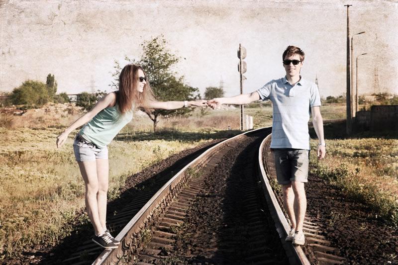 Suhtes naine ja mees raudteel käsikäes