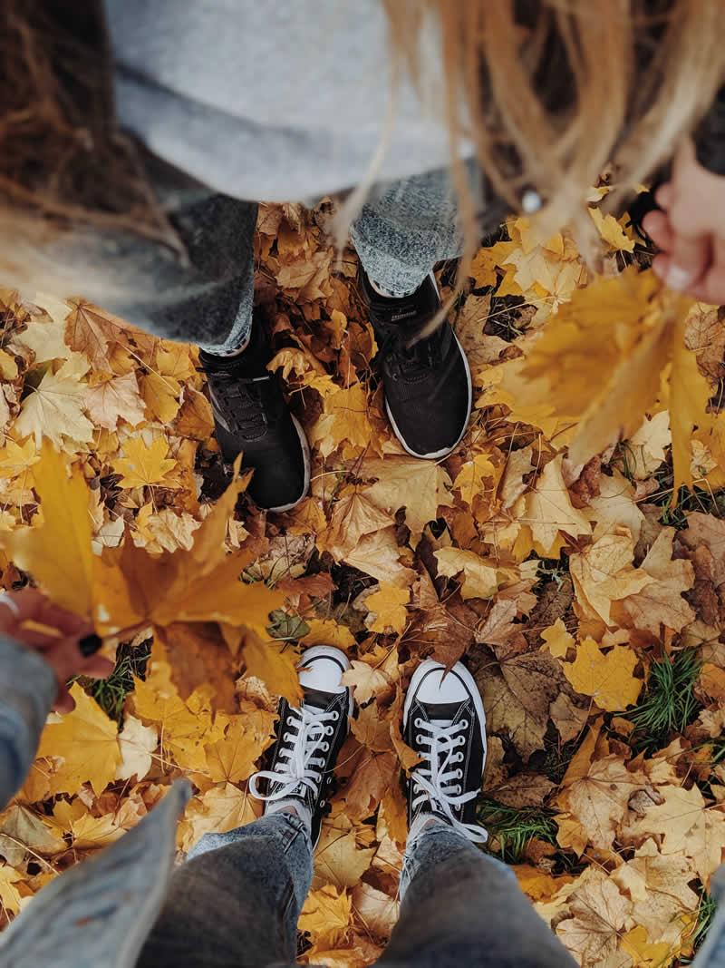 Kaaslasega sügisel lehtede sees