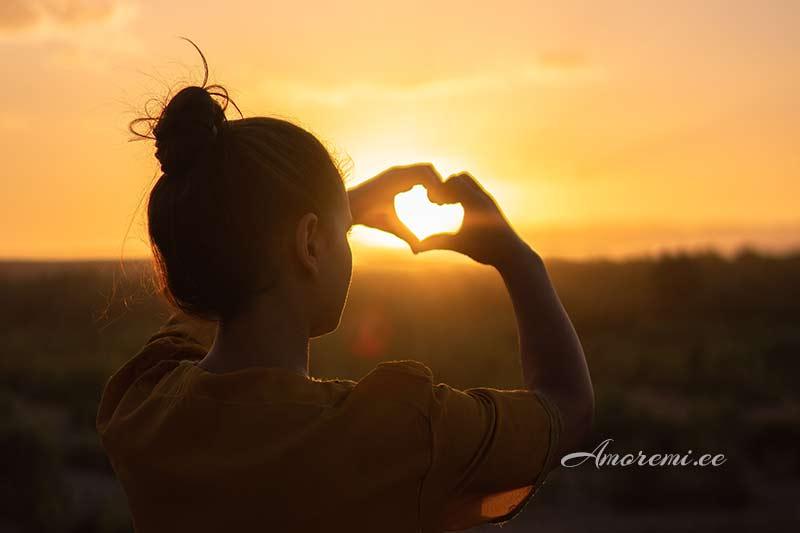 Naine teeb päikesele südame