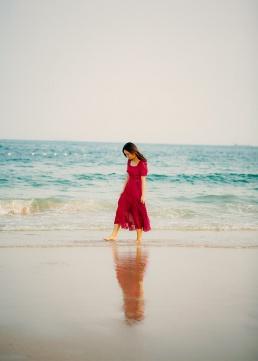 Naine punases jalutab rannas